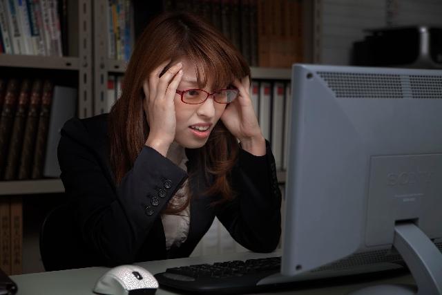 パソコンを見つめる女性の画像