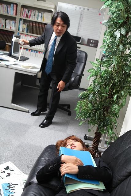 会社で眠る女性の画像