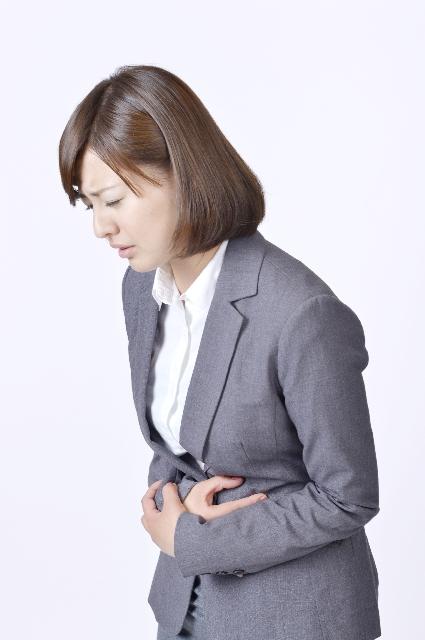 下痢でお腹を押さえる女性の画像