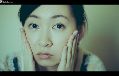 顔に手を添える女性の画像