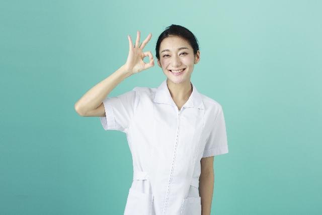 オッケーサインをする白衣の女性の画像