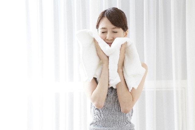 顔をタオルで拭く女性の画像