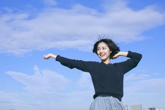 背伸びをする女性の画像