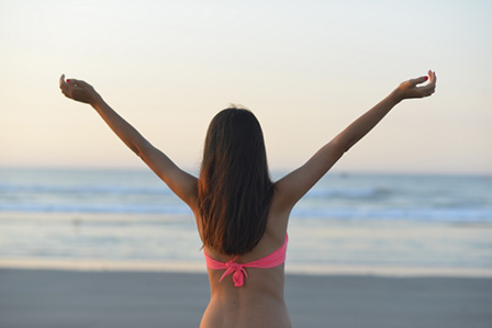 背中を見せる水着の女性の画像