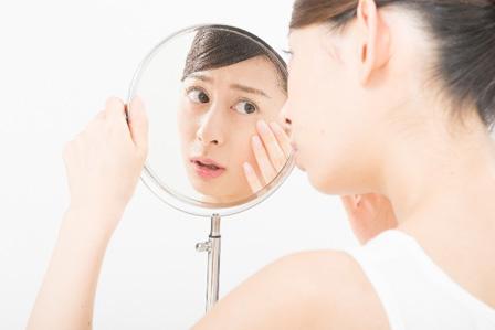鏡をみる女性の画像