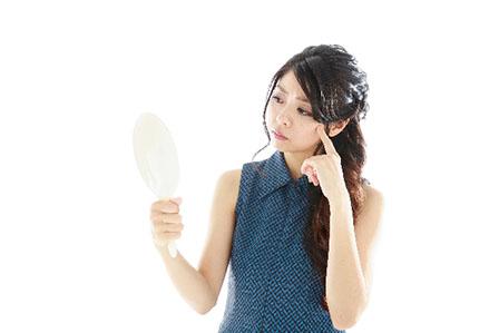 鏡を見る女性の画像