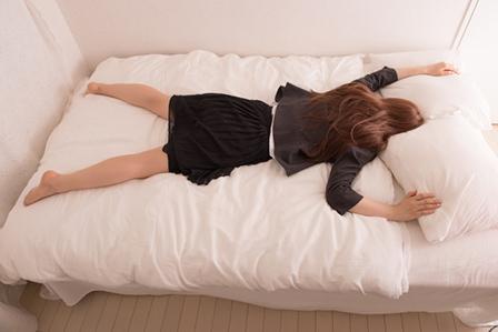 ベットで寝る女性の画像